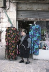The Time stop is in Mea Searim.   Aged woman stands on the street